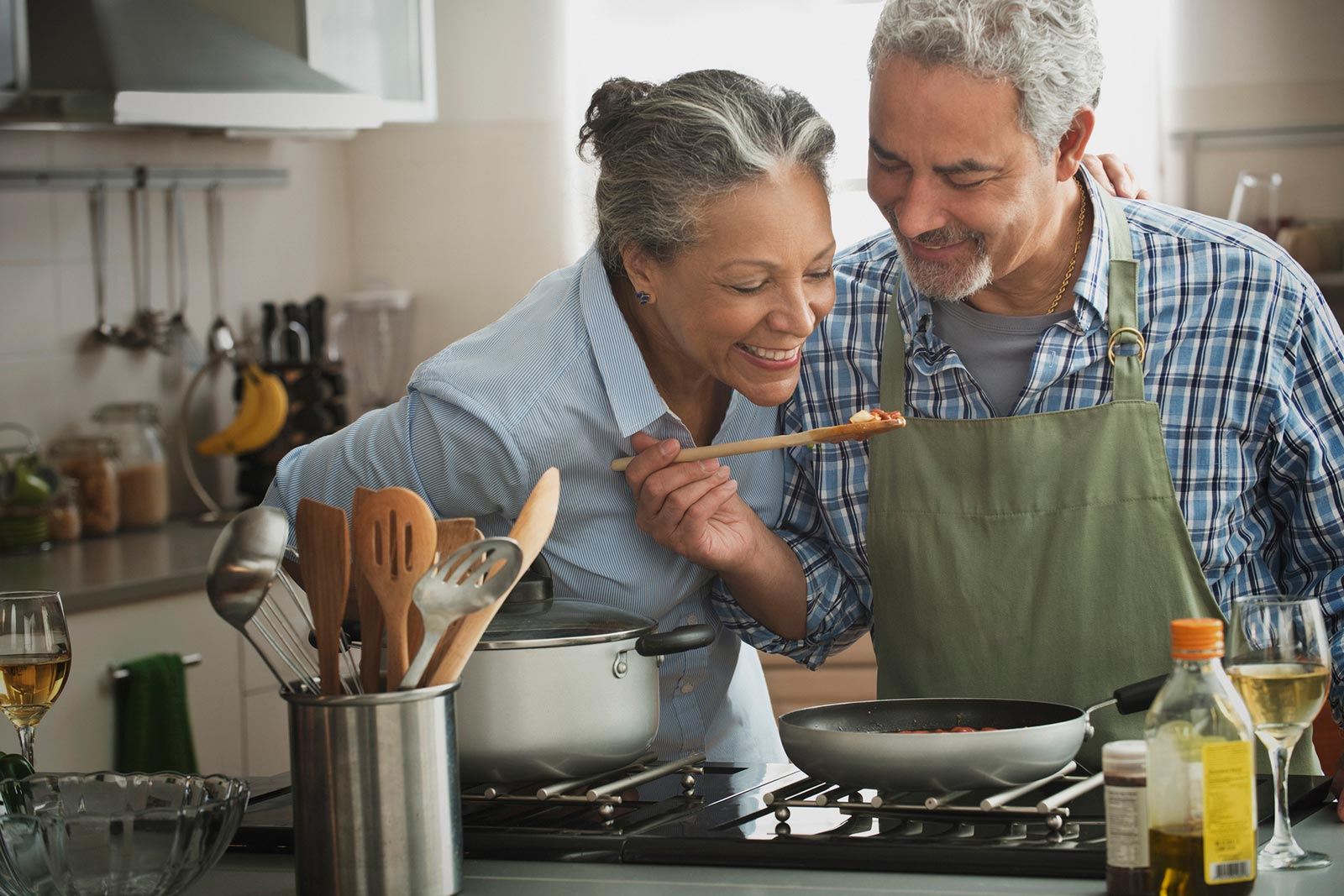 older woman and older man cooking together at stove