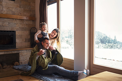 mom, dad, daughter playing in front of fireplace and window