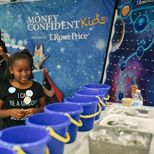 A child plays a game to learn about finance at an T. Rowe Price event.