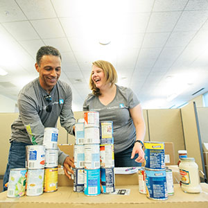 Two associates collect food to support global hunger relief.