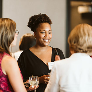 Women attend a networking event to promote gender equity in financial services.