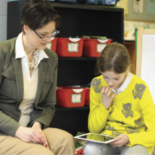 A T. Rowe Price associate helps a child learn about money management on her tablet.